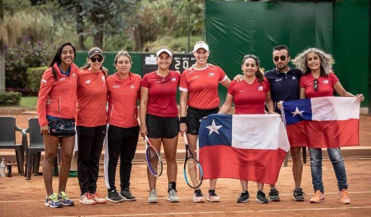 Equipo femenino de tenis chileno y equipo técnico. 7 mujeres y 1 hombre en total. Dos mujeres portan banderas de Chile
