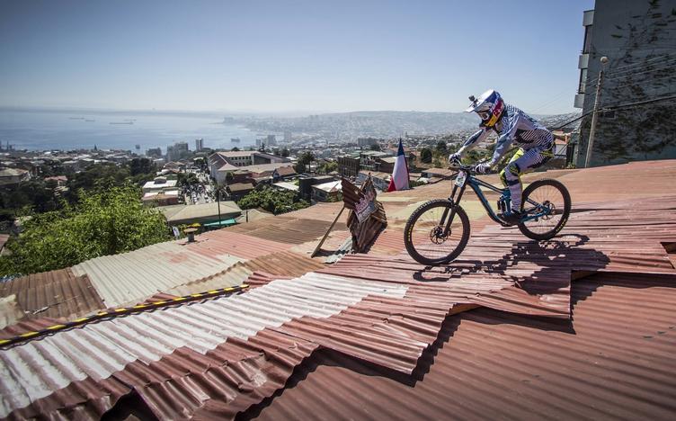 Ciclista bajando por el techo de una casa en una competencia de descenso