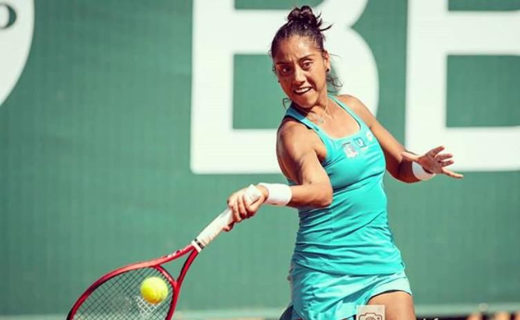 Tenista Daniela Seguel con tenida de color verde, golpea una pelota de tenis con su raqueta, la cual sostiene con la mano derecha